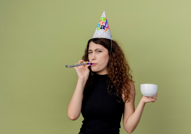 Young beautiful woman with curly hair in a holiday cap blowing whistle holding coffee cup looking displesed birthday party concept  over light