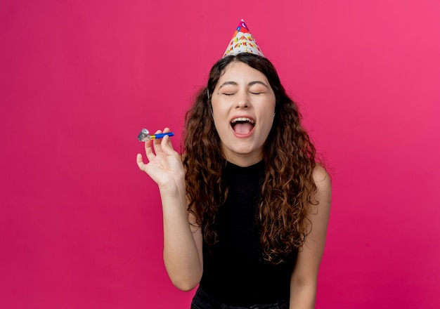 Young beautiful woman with curly hair in a holiday cap crazy happy birthday party concept standing over pink wall