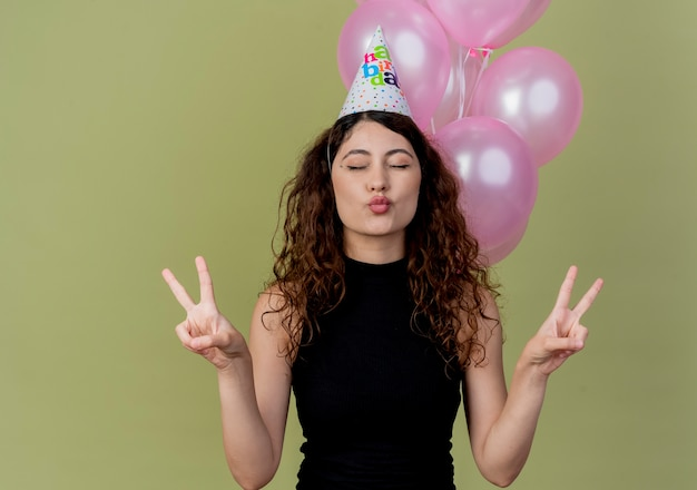 Young beautiful woman with curly hair in a holiday cap happy and positive showing v-sign with closed eyes standing with air balloons over light wall