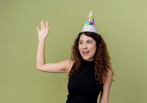 Young beautiful woman with curly hair in a holiday cap happy and positive waving with hand birthday party concept standing over light wall