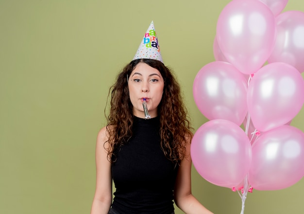 Young beautiful woman with curly hair in a holiday cap holding air balloons blowing whistle happy and positive celebrating birthday party standing over light wall