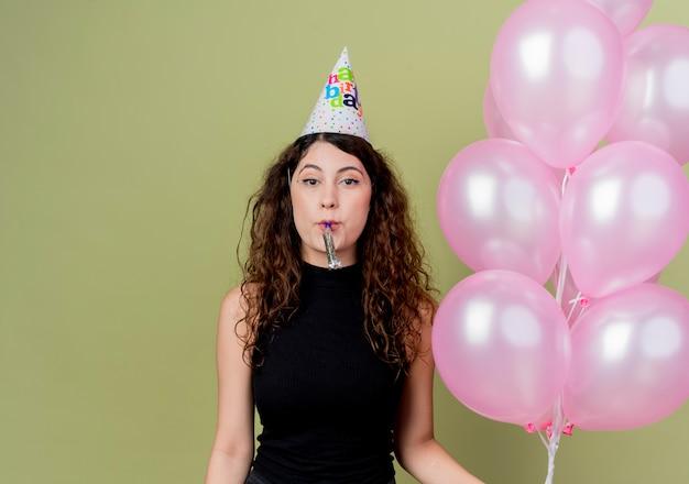 Giovane bella donna con capelli ricci in una protezione di vacanza che tiene gli aerostati di aria che soffia fischio felice e positivo che celebra la festa di compleanno che sta sopra la parete chiara