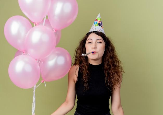 Giovane bella donna con i capelli ricci in una protezione di vacanza che tiene gli aerostati di aria che soffia fischio felice e positivo che celebra la festa di compleanno che sta sopra la parete chiara