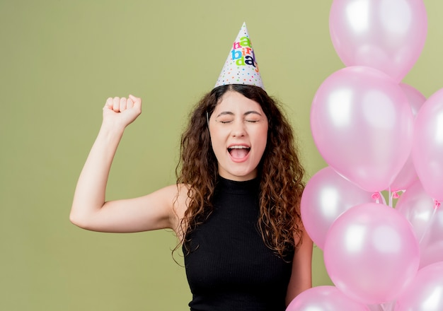 Young beautiful woman with curly hair in a holiday cap holding air balloons clenching fist crazy happy birthday party concept standing over light wall
