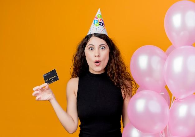 Giovane bella donna con i capelli ricci in una protezione di vacanza che tiene gli aerostati di aria e il lookign della carta di credito ha sorpreso il concetto della festa di compleanno che sta sopra la parete arancione