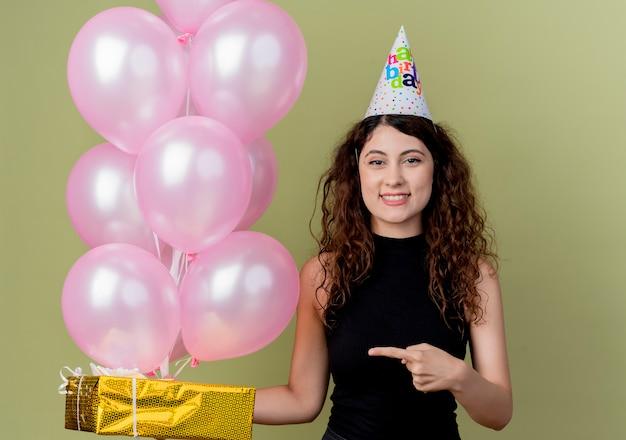Giovane bella donna con i capelli ricci in un berretto da vacanza in possesso di palloncini d'aria e confezione regalo puntando il dito contro di esso sorridendo allegramente felice e positivo in piedi sopra la parete chiara