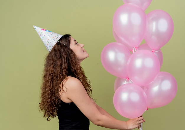 Young beautiful woman with curly hair in a holiday cap holding air balloons happy and excited birthday party concept standing sideways over light wall