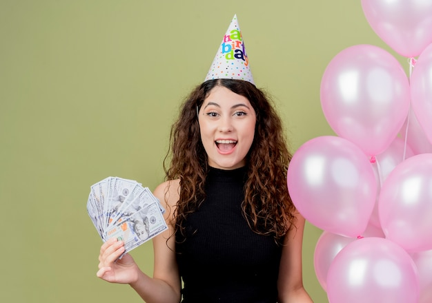 Young beautiful woman with curly hair in a holiday cap holding air balloons happy and excited showing cash birthday party concept standing over light wall