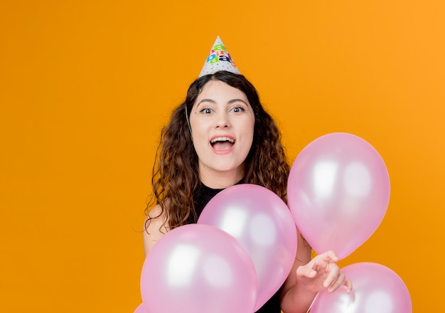 Giovane bella donna con i capelli ricci in una protezione di vacanza che tiene gli aerostati di aria happyand eccitato concetto di festa di compleanno in piedi sopra la parete arancione