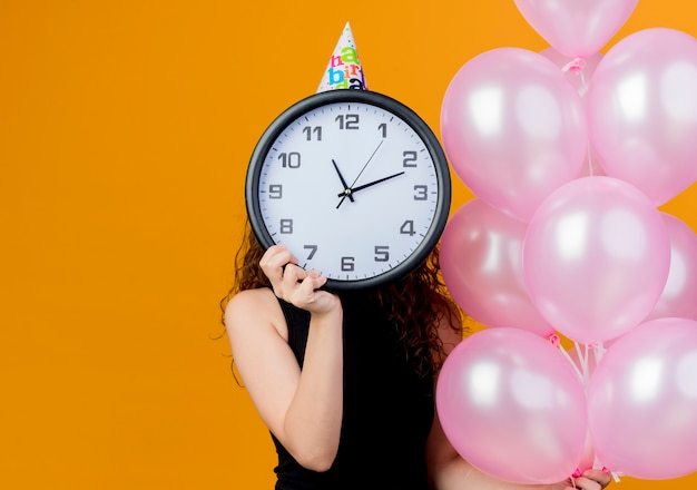 Young beautiful woman with curly hair in a holiday cap holding air balloons hiding face behind wall clock birthday party concept standing over orange wall