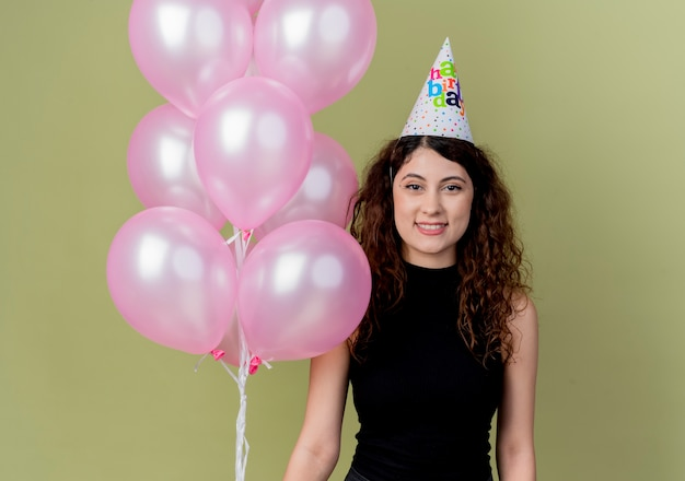Young beautiful woman with curly hair in a holiday cap holding air balloons lookign at camera smiling happy and positive  over light