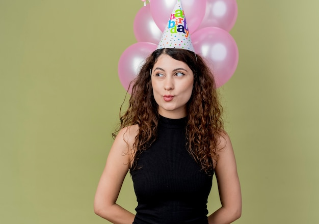 Young beautiful woman with curly hair in a holiday cap holding air balloons looking aside happy and positive birthday party concept standing over light wall