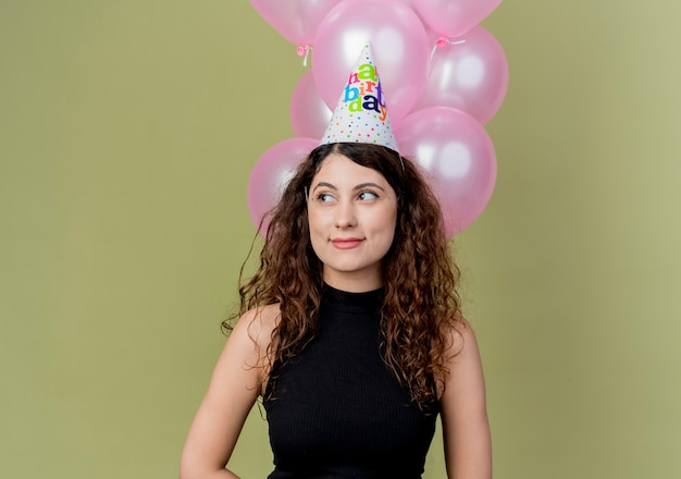 Young beautiful woman with curly hair in a holiday cap holding air balloons looking aside with smile on face birthday party concept standing over light wall