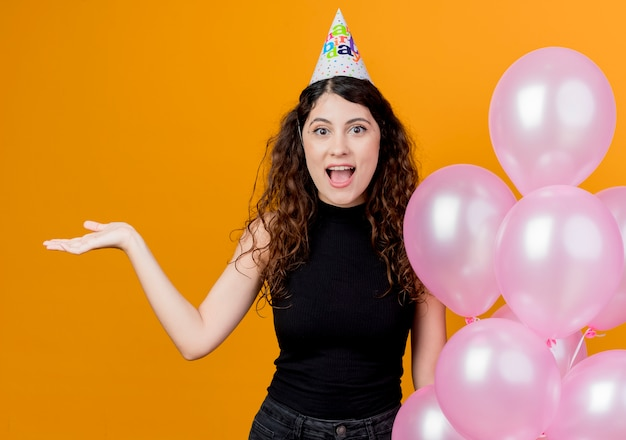 Young beautiful woman with curly hair in a holiday cap holding air balloons presenting something with arm of hand happy and excited birthday party concept  over orange