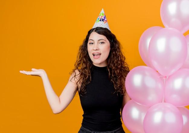 Giovane bella donna con i capelli ricci in un cappello di vacanza che tiene gli aerostati di aria che presentano qualcosa con il braccio che sorride allegramente concetto di festa di compleanno in piedi sopra la parete arancione