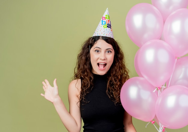 Young beautiful woman with curly hair in a holiday cap holding air balloons raising hand happy and excited smiling cheerfully birthday party concept standing over light wall