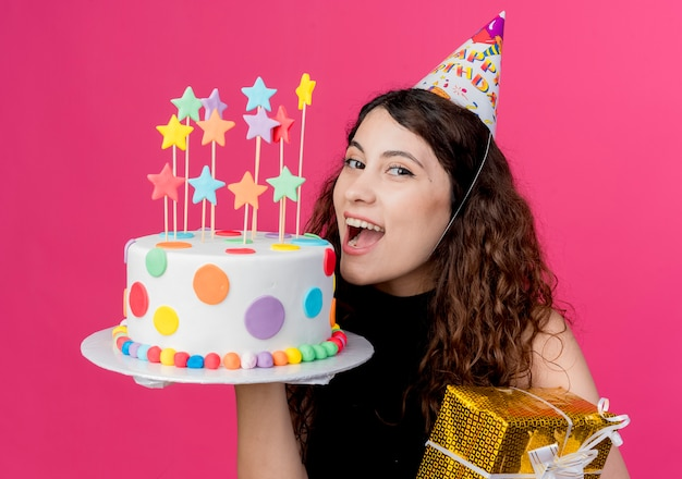 Giovane bella donna con capelli ricci in una protezione di festa che tiene la torta di compleanno e il concetto di festa di compleanno felice ed emozionato del contenitore di regalo sopra il rosa