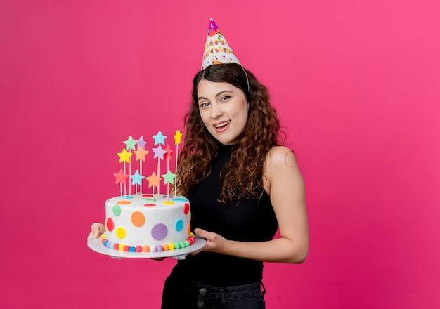 Giovane bella donna con capelli ricci in una protezione di festa che tiene il concetto di festa di compleanno felice e positivo della torta di compleanno che sta sopra la parete rosa