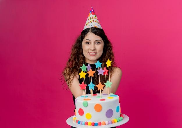 Giovane bella donna con capelli ricci in una protezione di festa che tiene la torta di compleanno felice e concetto sorridente positivo della festa di compleanno che sta sopra la parete rosa