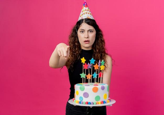 Giovane bella donna con capelli ricci in una protezione di festa che tiene la torta di compleanno che indica con il concetto scontento della festa di compleanno del dito che sta sopra la parete rosa
