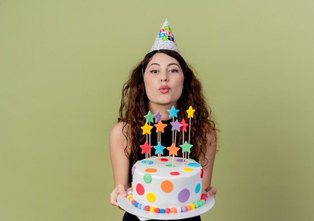 Young beautiful woman with curly hair in a holiday cap holding birthday cake smiling cheerfully happy and joyful  over light