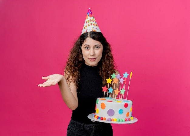 Young beautiful woman with curly hair in a holiday cap holding birthday cake  smiling with arm out as asking birthday party concept standing over pink wall