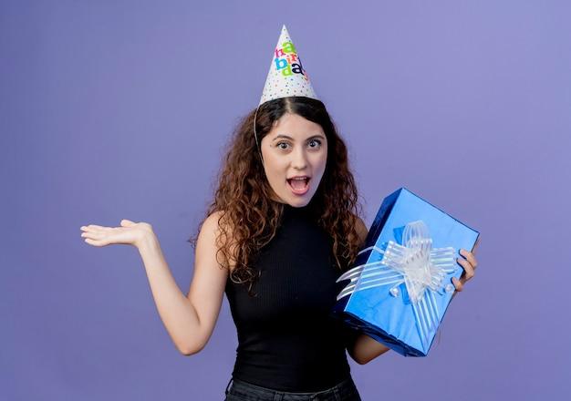 Giovane bella donna con capelli ricci in una protezione di festa che tiene il contenitore di regalo di compleanno che sembra stupito e sorpreso il concetto della festa di compleanno che sta sopra la parete blu