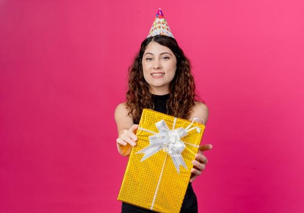 Giovane bella donna con capelli ricci in una protezione di vacanza che tiene il contenitore di regalo di compleanno che sorride allegramente concetto di festa di compleanno sopra il rosa