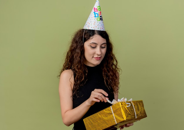 Young beautiful woman with curly hair in a holiday cap holding gift box looking at it with smile on face birthday party concept standing over light wall