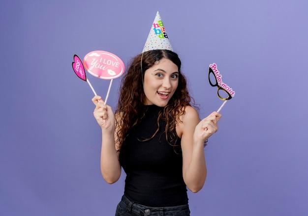 Giovane bella donna con capelli ricci in una protezione di festa che tiene la maschera di festa della tenuta che sorride allegramente concetto di festa di compleanno che sta sopra la parete blu