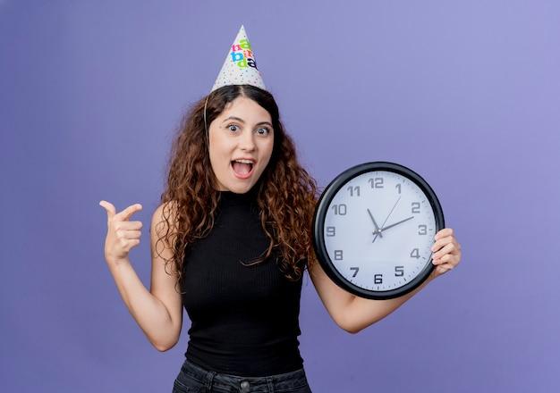 Giovane bella donna con capelli ricci in una protezione di vacanza che tiene l'orologio di parete che sorride allegramente concetto di festa di compleanno in piedi sopra la parete blu