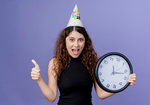 Giovane bella donna con capelli ricci in una protezione di vacanza che tiene l'orologio di parete che sorride allegramente che mostra i pollici in su concetto della festa di compleanno che sta sopra la parete blu