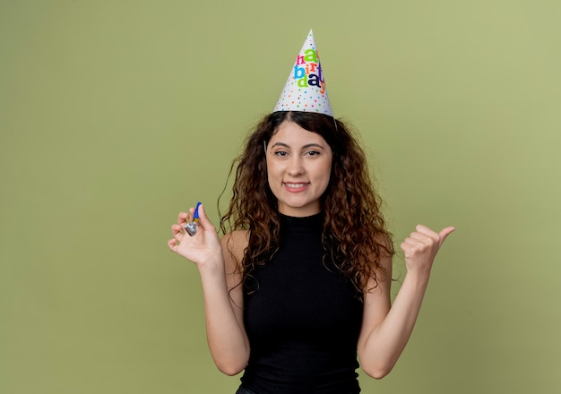 Young beautiful woman with curly hair in a holiday cap holding whistle smiling cheerfully birthday party concept standing over light wall