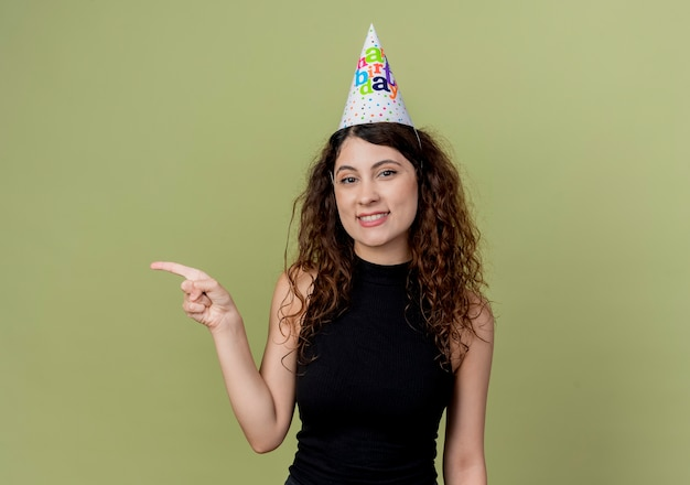 Young beautiful woman with curly hair in a holiday cap  pointign with finger to the side smiling cheerfully birthday party concept standing over light wall
