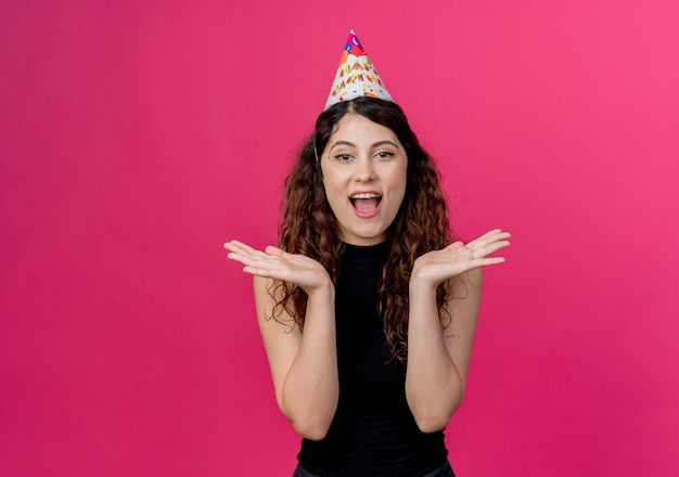 Young beautiful woman with curly hair in a holiday cap  surprised and happy birthday party concept standing over pink wall