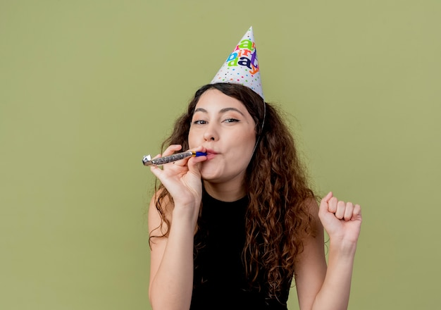 Young beautiful woman with curly hair in a holiday capblowing whistle happy and positive birthday party concept  over light