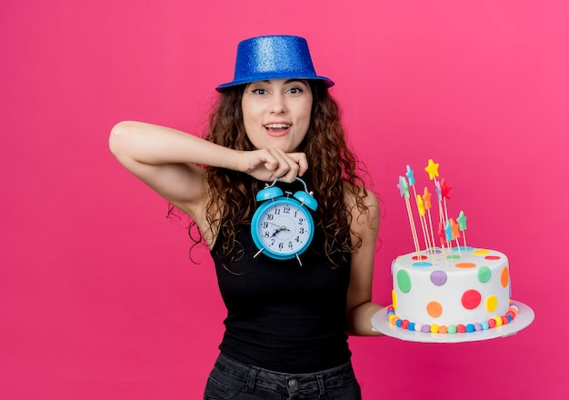 Young beautiful woman with curly hair in a holiday hat holding birthday cake and alarm clock looking surprised and happy birthday party concept standing over pink wall