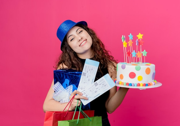 Young beautiful woman with curly hair in a holiday hat holding birthday cake gift box and air tickets happy and pleased smiling cheerfully birthday party concept over pink