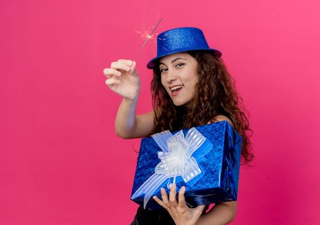 Giovane bella donna con capelli ricci in un cappello di festa che tiene il contenitore di regalo di compleanno e il concetto felice e allegro della festa di compleanno dello sparkler che sta sopra il muro rosa