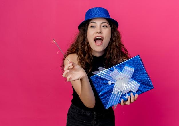 Giovane bella donna con capelli ricci in un cappello di festa che tiene il contenitore di regalo di compleanno e il concetto felice ed emozionante della festa di compleanno dello sparkler sopra il rosa