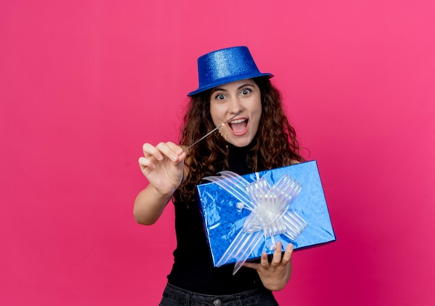 Young beautiful woman with curly hair in a holiday hat holding birthday gift box and sparkler happy and excited birthday party concept standing over pink wall