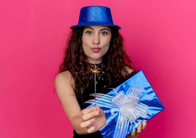 Giovane bella donna con capelli ricci in un cappello di festa che tiene il contenitore di regalo di compleanno e il concetto felice e gioioso della festa di compleanno dello sparkler sopra il rosa