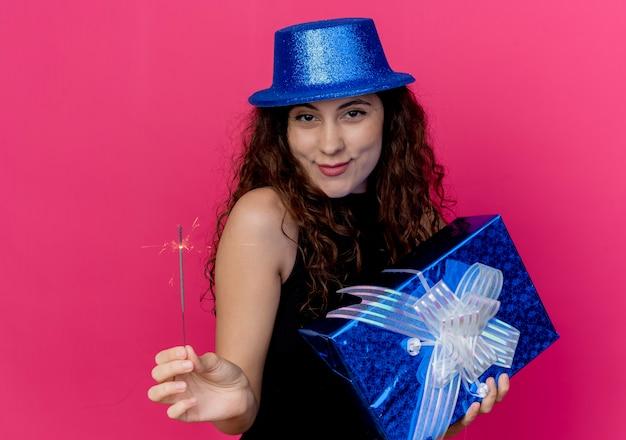 Giovane bella donna con i capelli ricci in un cappello di festa che tiene il contenitore di regalo di compleanno e il concetto sorridente felice e positivo della festa di compleanno dello sparkler che sta sopra il muro rosa