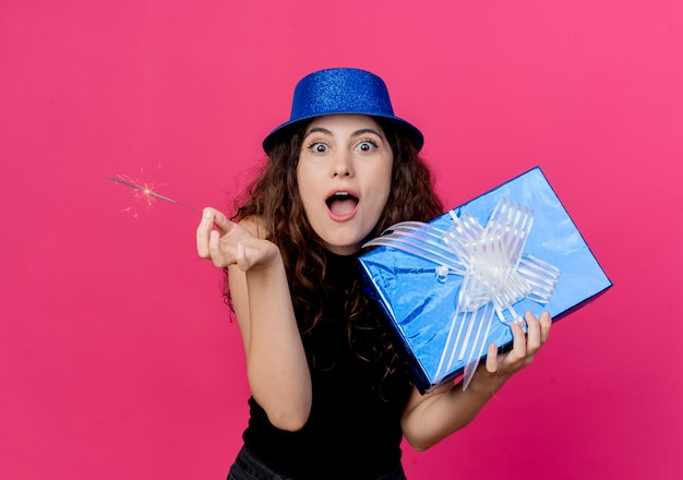 Young beautiful woman with curly hair in a holiday hat holding birthday gift box and sparkler surprised and amazed birthday party concept over pink