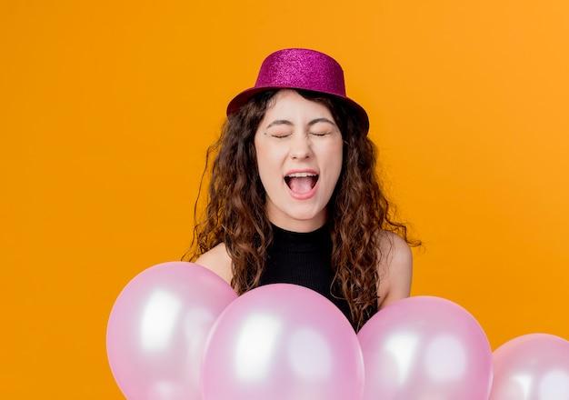 Giovane bella donna con capelli ricci in un cappello di festa che tiene il mazzo di palloncini d'aria pazzo felice urlando concetto di festa di compleanno in piedi sopra la parete arancione