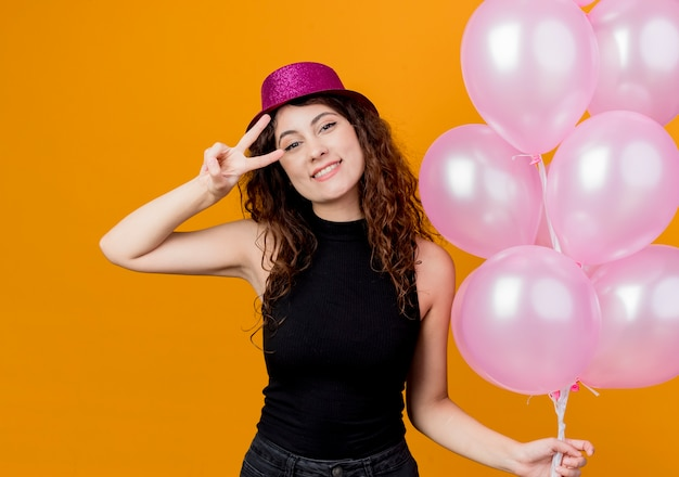 Giovane bella donna con i capelli ricci in un cappello di festa che tiene il mazzo di mongolfiere sorridente felice e positivo che mostra allegramente il concetto di festa di compleanno di v-segno in piedi sopra la parete arancione