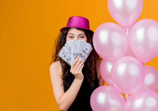 Young beautiful woman with curly hair in a holiday hat holding bunch of air balloons showing cash happy and excited birthday party concept standing over orange wall