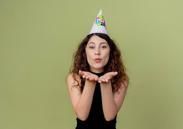 明るい壁の上に立っている彼女の誕生日パーティーのコンセプトの前に手でキスを吹くホリデーキャップの巻き毛の若い美しい女性