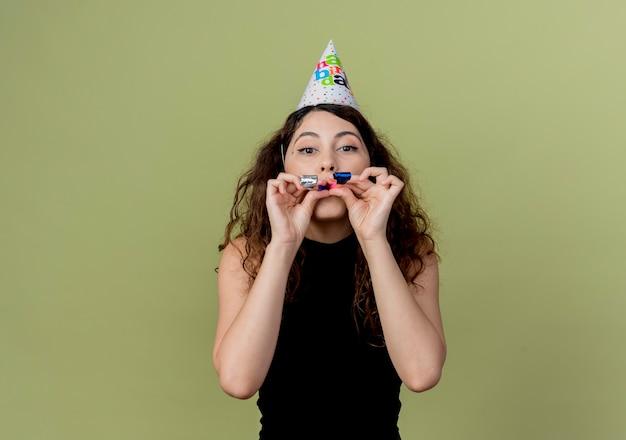 휴일 모자에 곱슬 머리를 가진 젊은 아름 다운 여자 빛 벽 위에 서 휘파람 행복하고 긍정적 인 생일 파티 개념