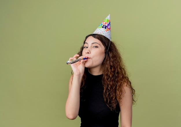 明るい壁の上に立ってホイッスル幸せでポジティブな誕生日パーティーのコンセプトを吹くホリデーキャップで巻き毛の若い美しい女性